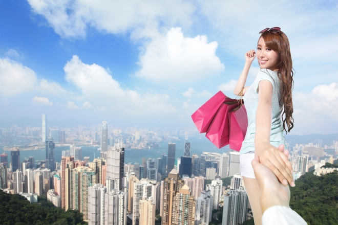 Happy Shopping in hong kong - beautiful young woman holding colored shopping bags with city background, asian